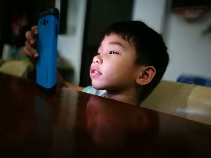 Close-Up Of Boy Using Smart Phone While Sitting At Table