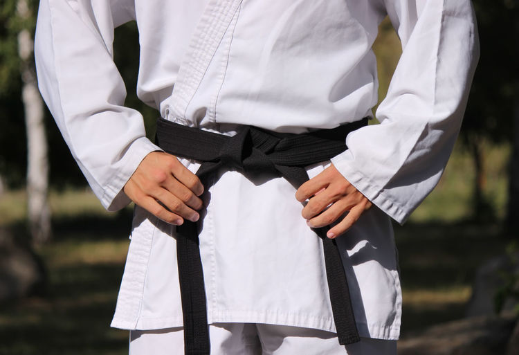 Midsection of karate man in uniform standing outdoors
