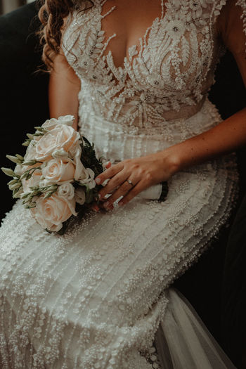 Midsection of bride holding bouquet while sitting on chair