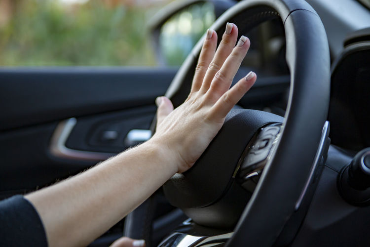 Midsection of woman using smart phone in car
