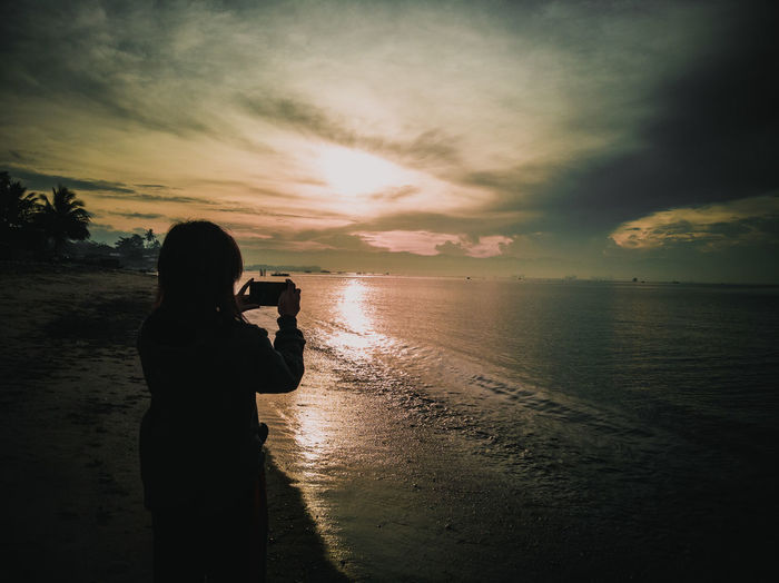 Silhouette woman photographing sea against during sunset
