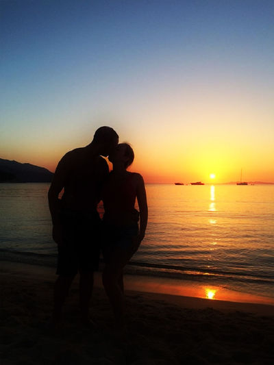Silhouette Of Couplte Kissing On Beach At Sunset