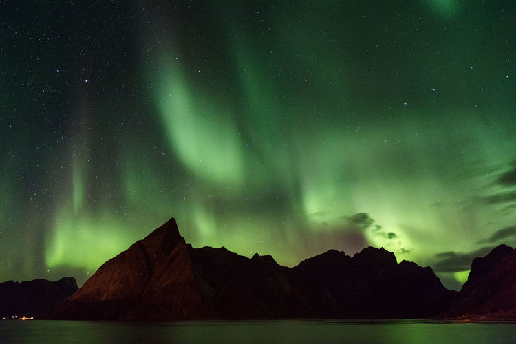 Northern lights over Olstind mountain, Lofoten, Norway Lofoten Norway Polar Lights Northern Lights Aurora Polaris Aurora Aurora Borealis Beauty In Nature Scenics - Nature Night Tranquil Scene Star - Space Sky Tranquility Astronomy Green Color Space Idyllic Mountain No People Water Nature Non-urban Scene Low Angle View Star Mountain Range