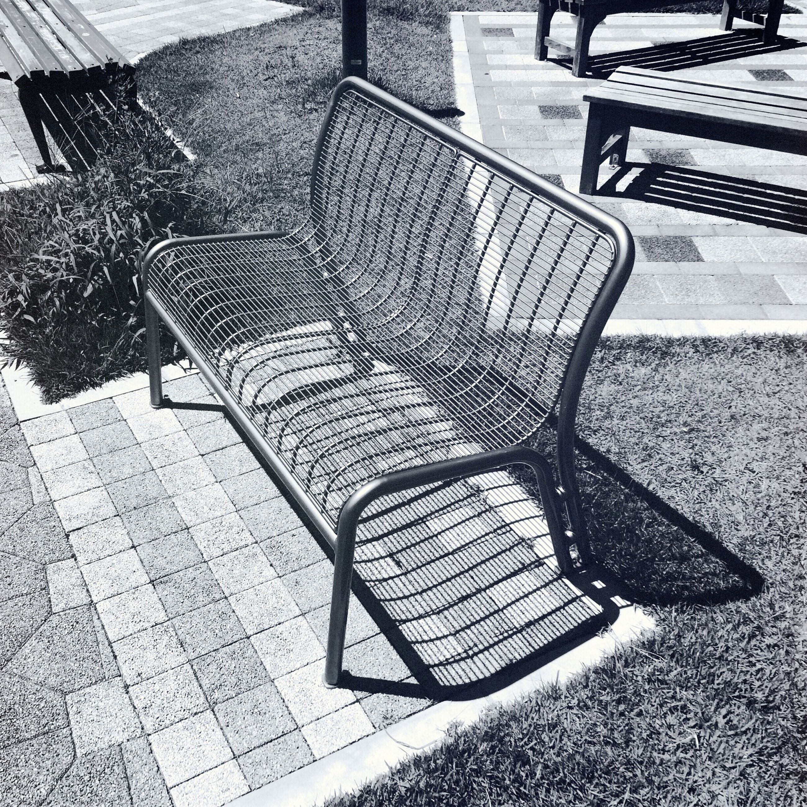 chair, empty, absence, seat, shadow, bench, high angle view, sunlight, cobblestone, paving stone, sidewalk, day, table, no people, outdoors, footpath, park bench, furniture, street, pattern