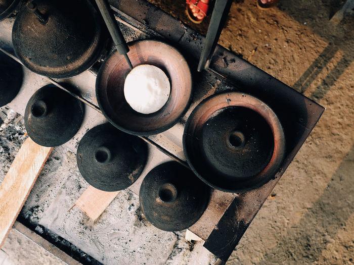 High angle view of surabi, indonesian pancake, cooked upon small earthenware frying pan.