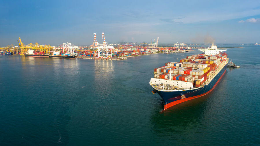 Aerial in front of smart cargo ship carrying container and running near international custom