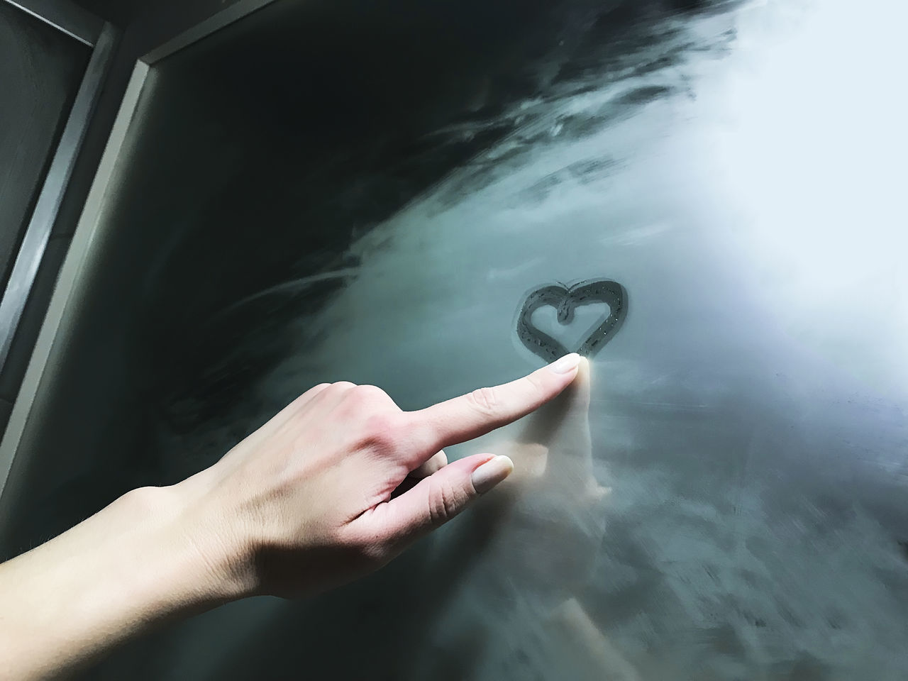 Cropped hand of woman drawing heart shape on wet mirror