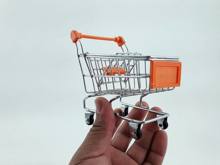 Close-up of hand holding shopping cart against white background