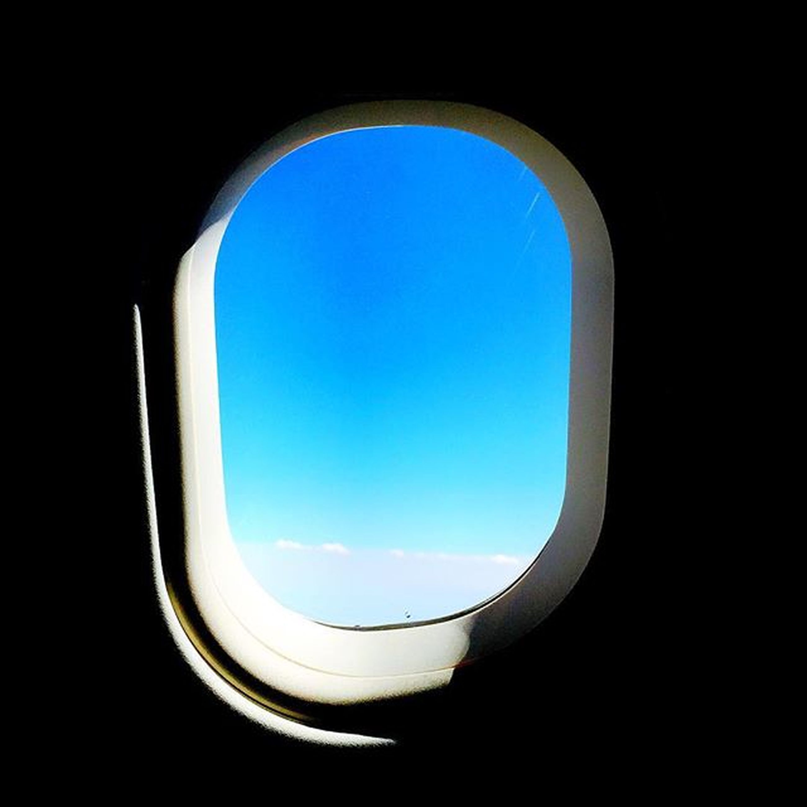 window, indoors, copy space, clear sky, airplane, circle, blue, air vehicle, sky, flying, transportation, transparent, glass - material, geometric shape, no people, nature, vehicle interior, mid-air, day, shape