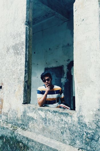 Young Man Standing By Window Of Abandoned Building