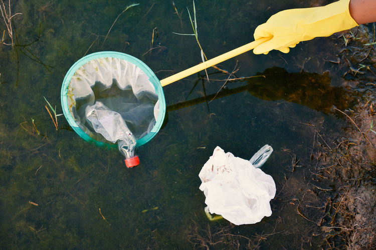 Cropped hand removing bottle from net floating in lake