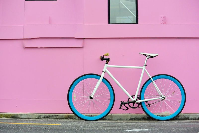 Bicycle parked against pink wall