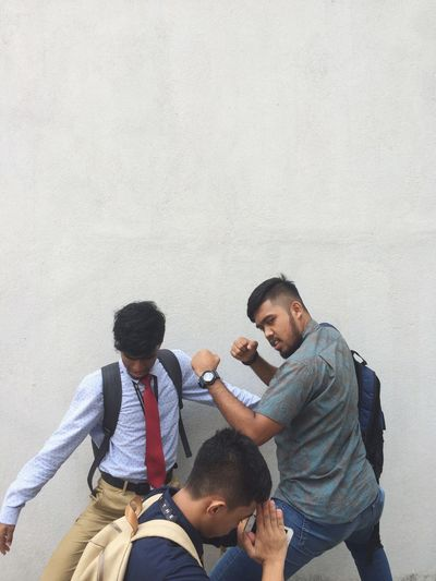 Friends posing against wall