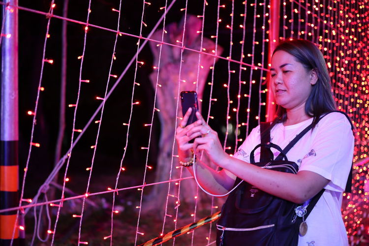 Woman using mobile phone by illuminated lighting equipment at night