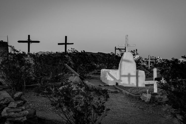 Cross in cemetery against sky