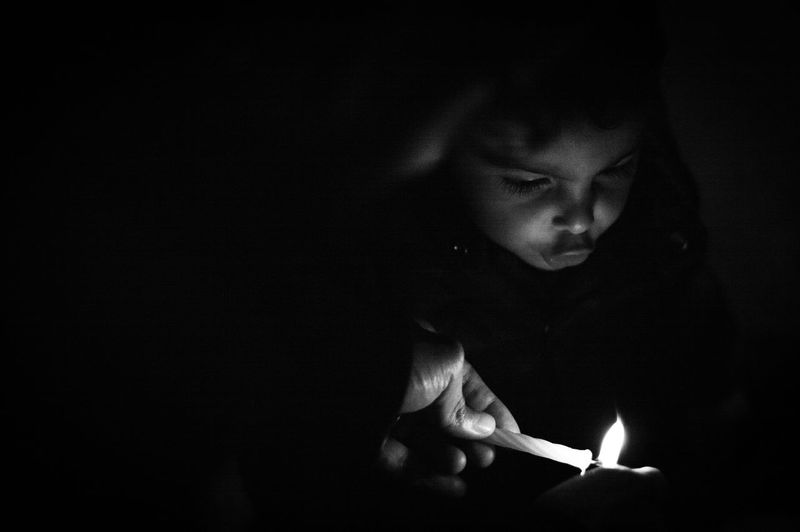 Low angle view of girl looking away against black background