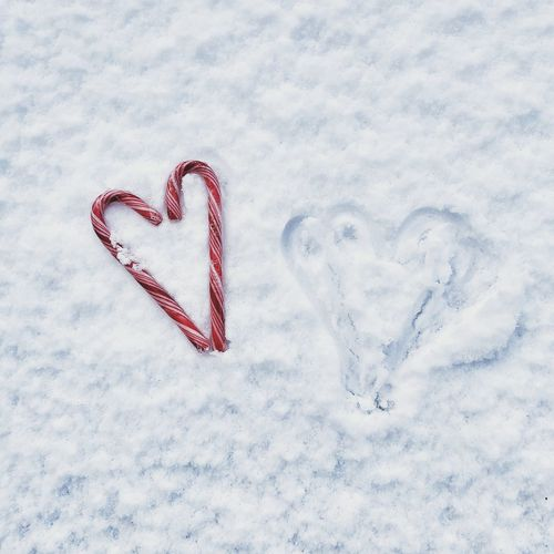 High angle view of heart shape made with candy canes on snow