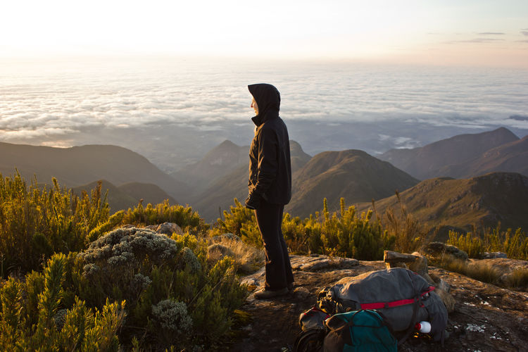 Side View Of Woman Standing On Mountain Against Cloudy Sky During Sunrise