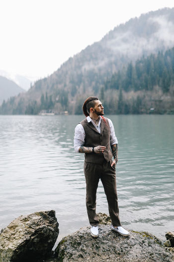 A tall brutal man hipster groom in a wedding suit stands by the misty mountains and lake in nature
