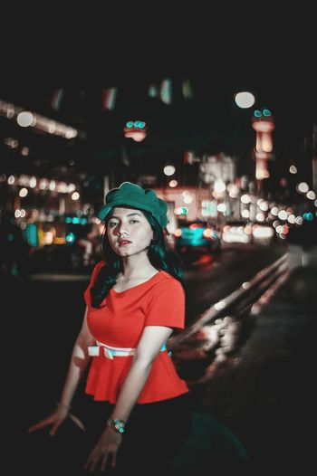 Portrait of young woman standing in city at night