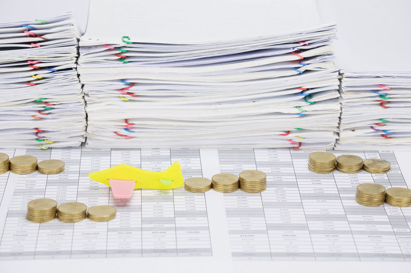 High angle view of stacked coins with airplane model on financial documents