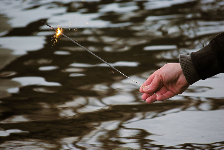 Cropped hand holding sparkler over lake