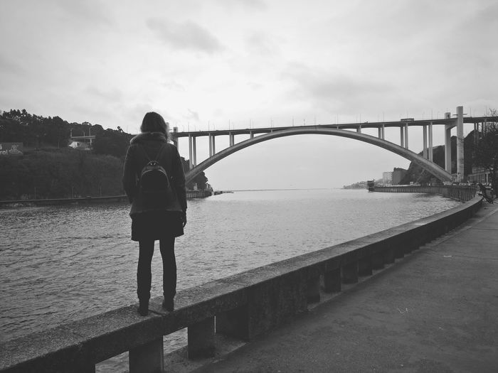 Rear view of woman standing on bridge