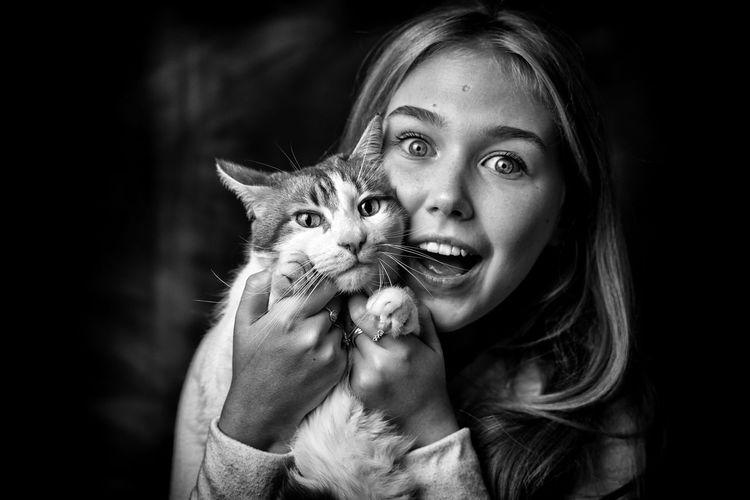 Portrait of smiling teenage girl holding cat