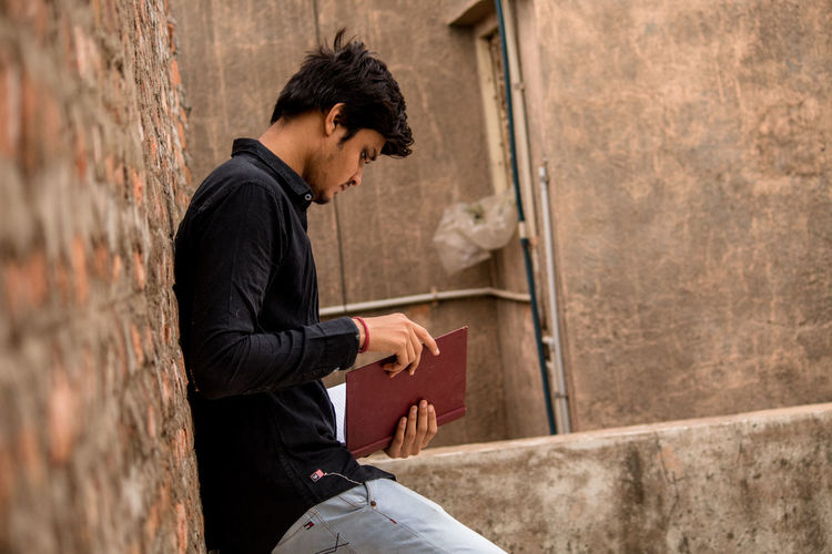 Young Man Reading Book While Standing Against Brick Wall