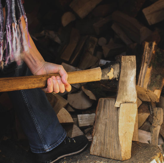Low section of man cutting wood with axe