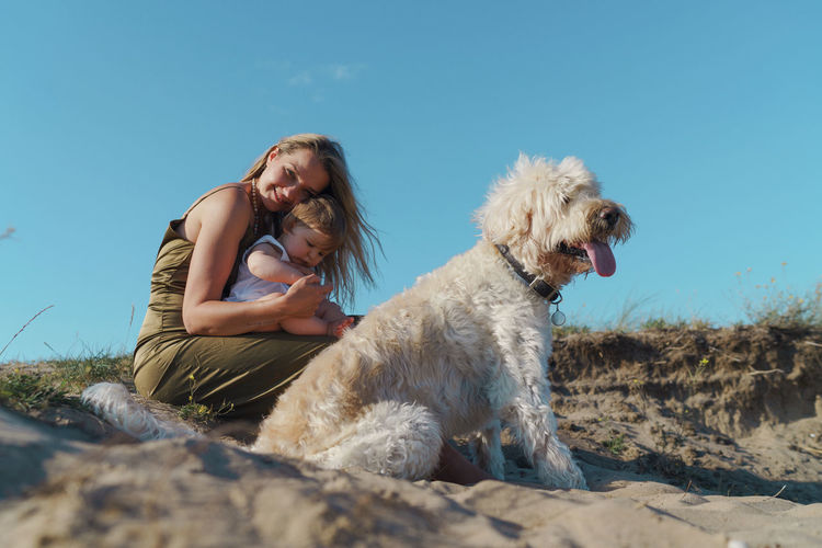 Woman with child and a dog sitting on land against sky