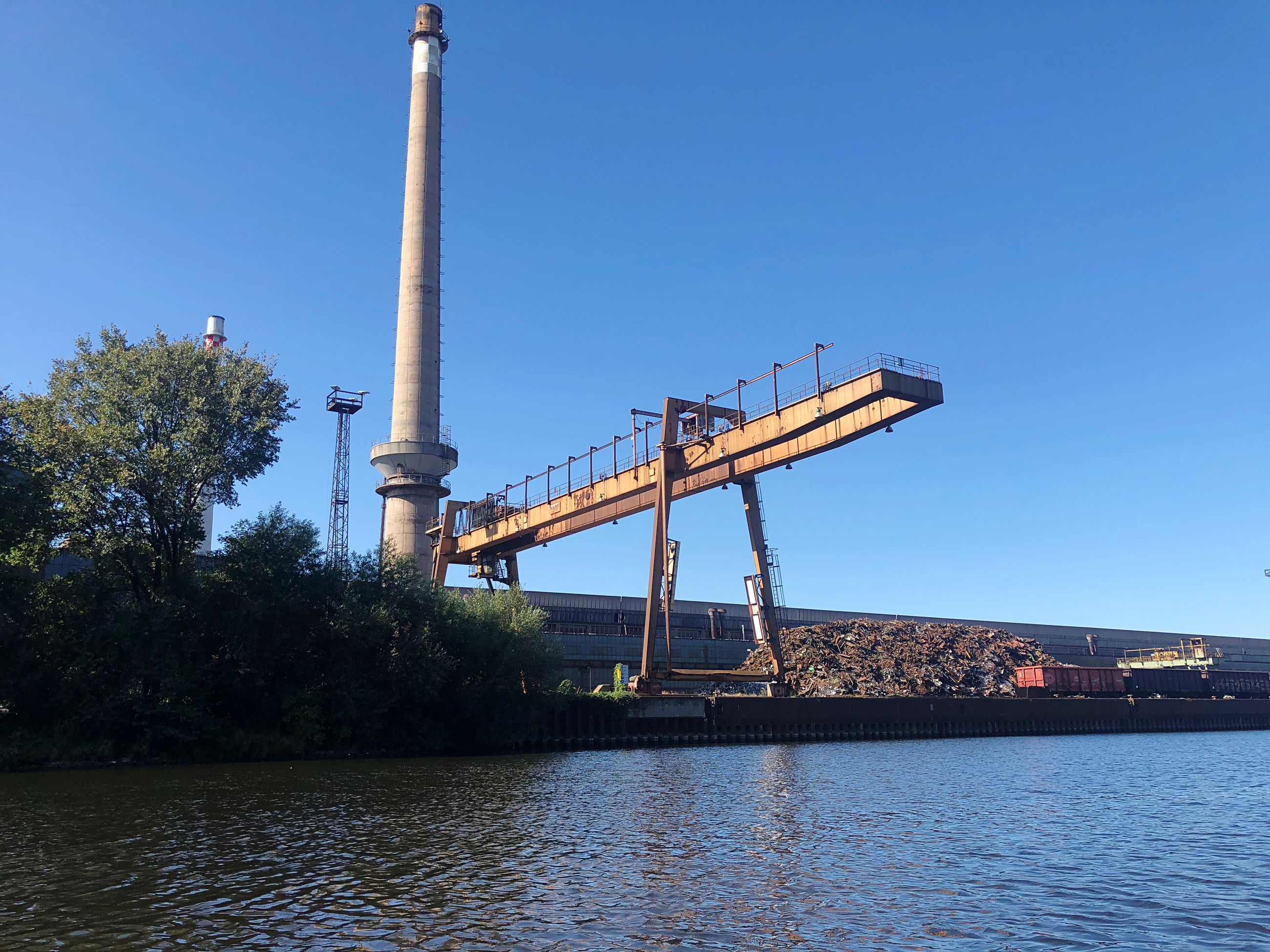 sky, water, clear sky, architecture, built structure, industry, nature, waterfront, no people, blue, building exterior, day, copy space, outdoors, river, plant, tree, factory, low angle view, industrial equipment