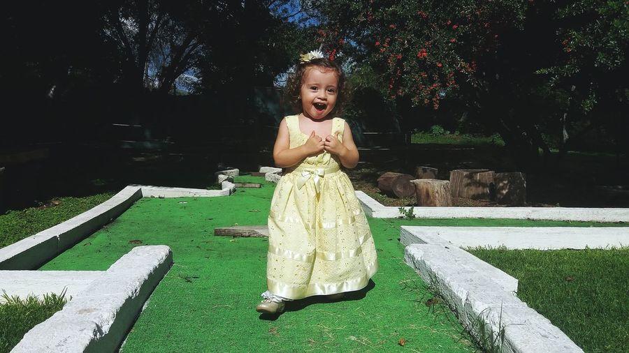 Portrait of shocked baby girl standing against trees