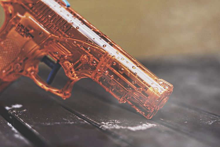 Close-up of wet toy gun on table