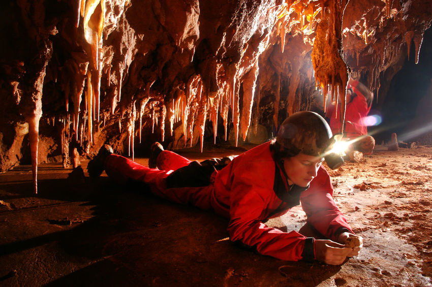 A Paleontologist studying fossils in a cave Acetylene Archeology Discovering Stalactite  Treasure Adventure Cave Caving Discovery Explorer Helmet Hidden Illuminated Nature One Person Paleontology People Red Rock Formation Sitting Speleology Spelunker Spelunking Spéléologie Stalagmite