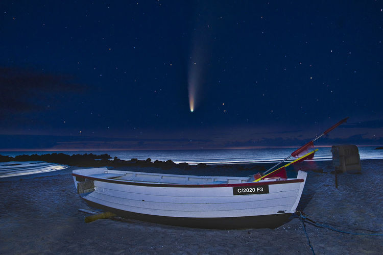 Boat moored on beach against sky at night