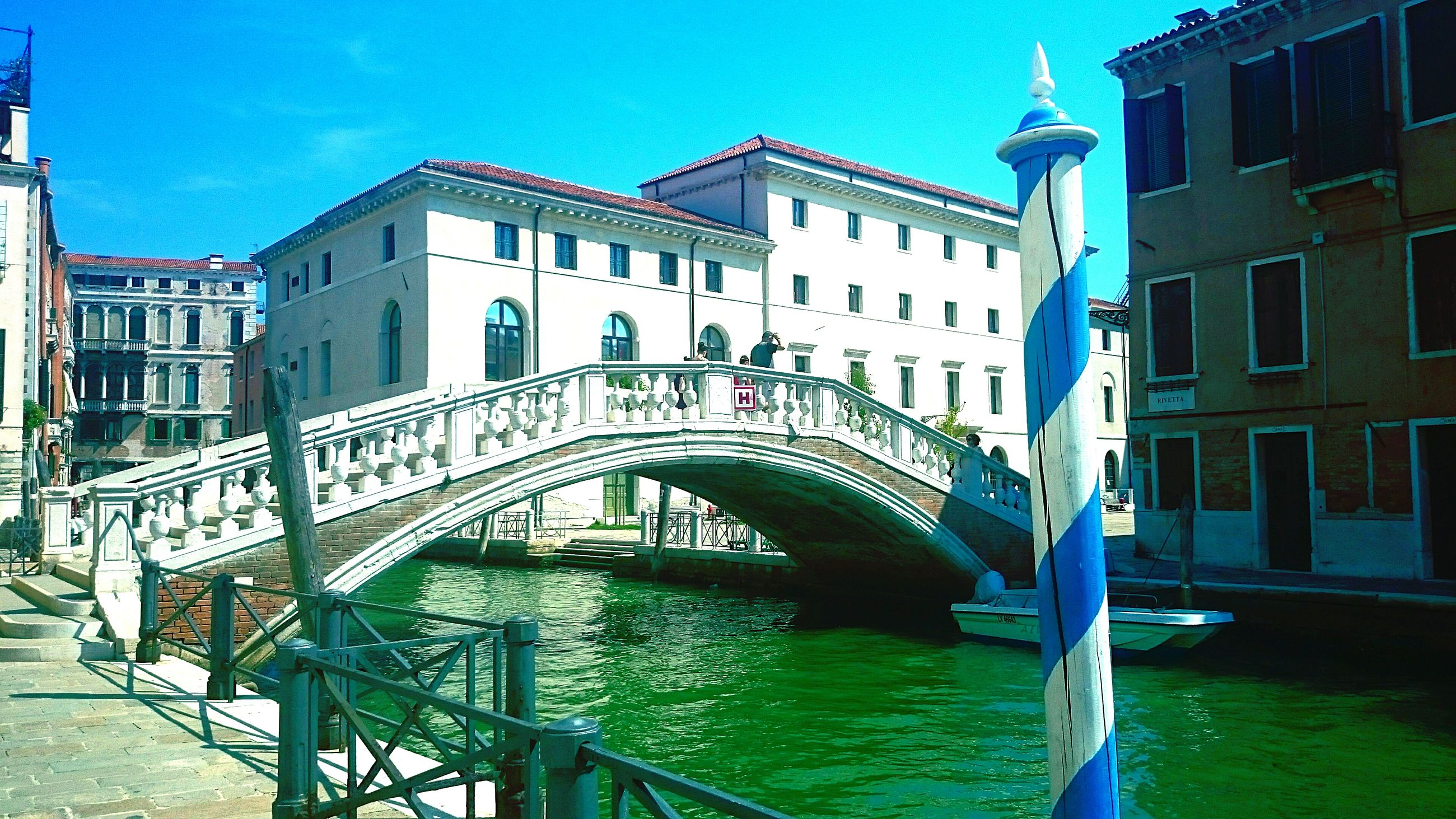 architecture, built structure, building exterior, railing, bridge - man made structure, water, connection, arch, canal, sky, blue, city, sunlight, clear sky, low angle view, building, day, arch bridge, river, bridge