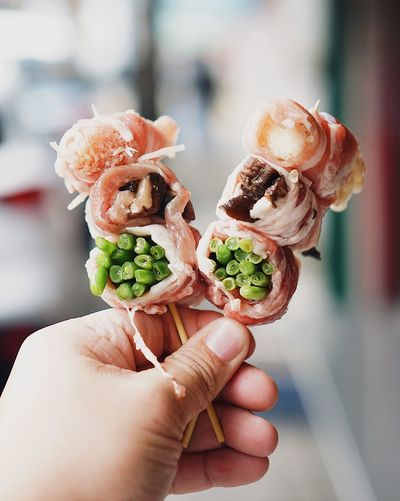 Cropped Hand Of Man Holding Skewer Meat Rolls