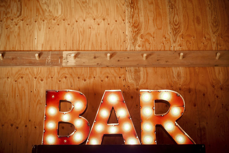 Bar sign Capital Letter Close-up Communication Flooring Illuminated Indoors  Information Information Sign Light Lighting Equipment Night No People Side By Side Sign Table Text Wall - Building Feature Western Script Wood Wood - Material