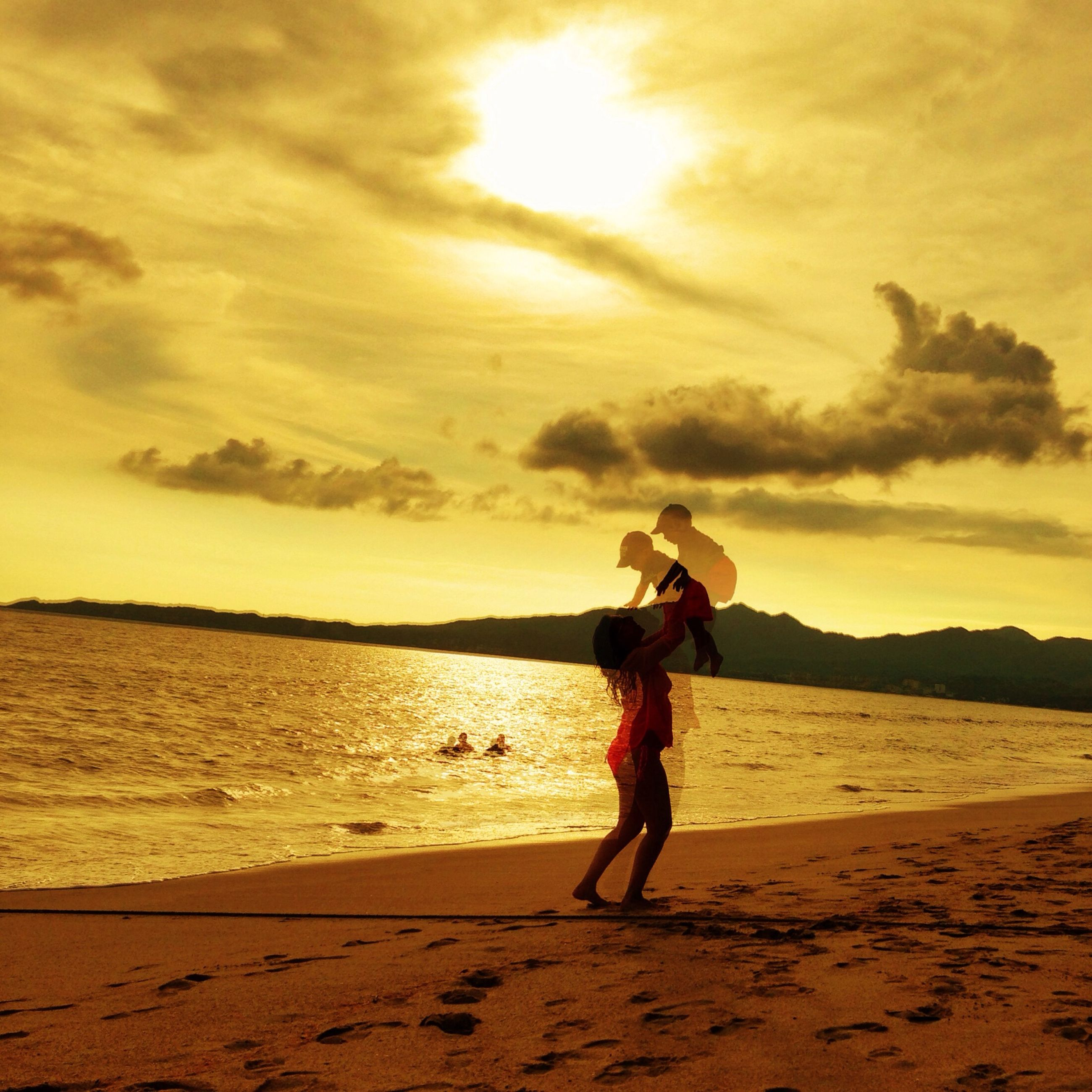 beach, sunset, full length, sky, sand, lifestyles, leisure activity, shore, sea, cloud - sky, standing, sunlight, beauty in nature, tranquil scene, vacations, tranquility, orange color, scenics