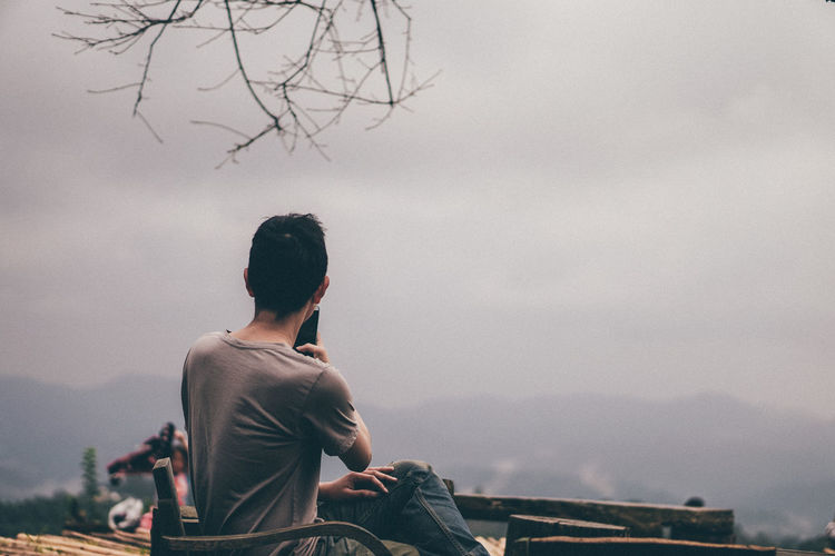 Side view of man photographing with smart phone while sitting on mountain against cloudy sky
