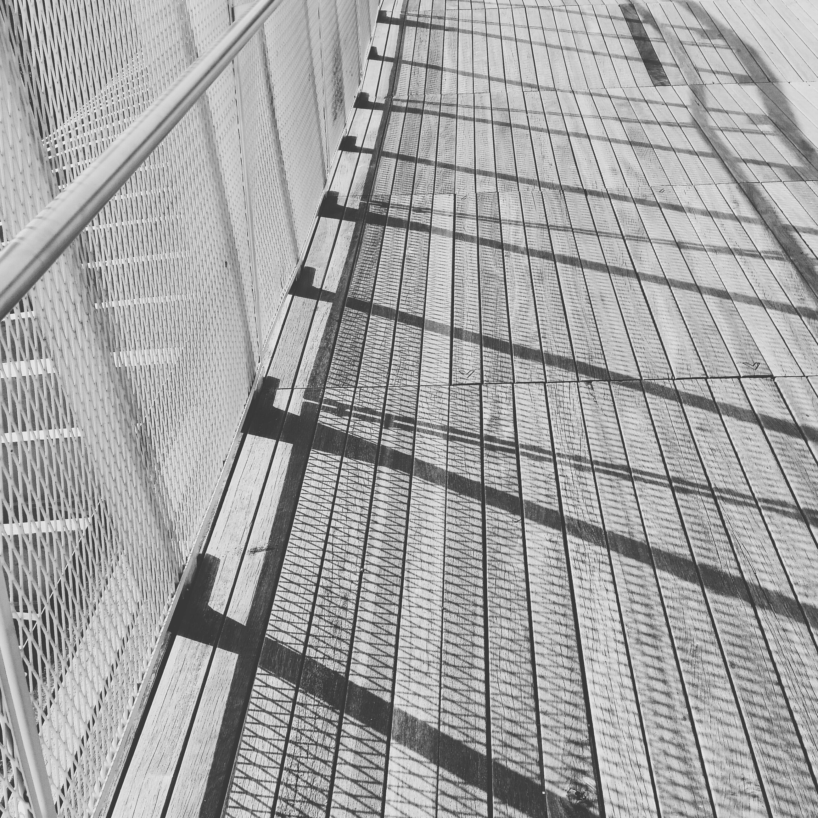 pattern, high angle view, shadow, railing, built structure, textured, sunlight, wall - building feature, day, no people, metal, steps, architecture, steps and staircases, outdoors, empty, design, the way forward, close-up, text