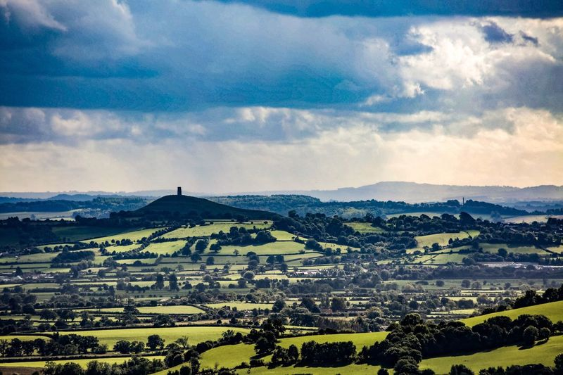 Glastonbury Tor quietly adorning the distant hill. Landscape Tranquil Scene Scenics Agriculture Beauty In Nature Nature Field Sky Rural Scene Tranquility Cloud - Sky No People Outdoors Day Patchwork Landscape Tree Glastonbury Tor