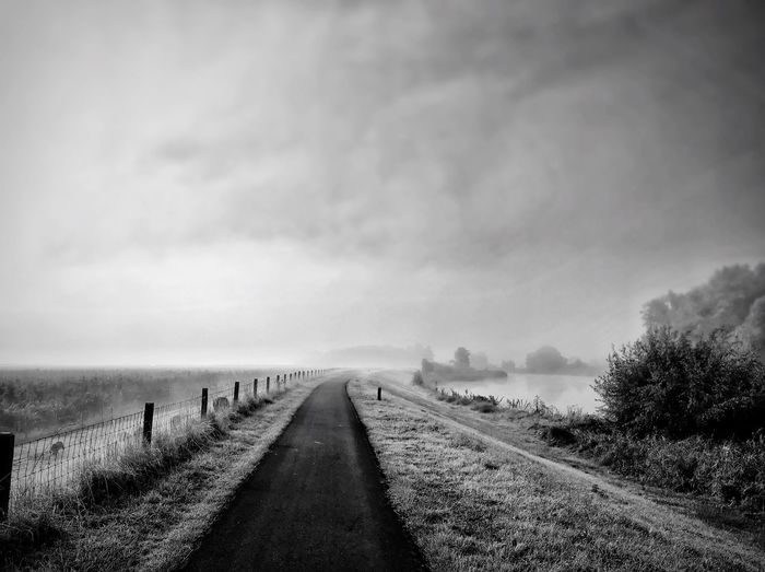 Octoberochtendmist The Way Forward Tranquil Scene Tree Tranquility Sky Landscape Scenics Diminishing Perspective Fence Day Water Non-urban Scene Nature Cloud - Sky Beauty In Nature Outdoors Vanishing Point Sea Long Narrow
