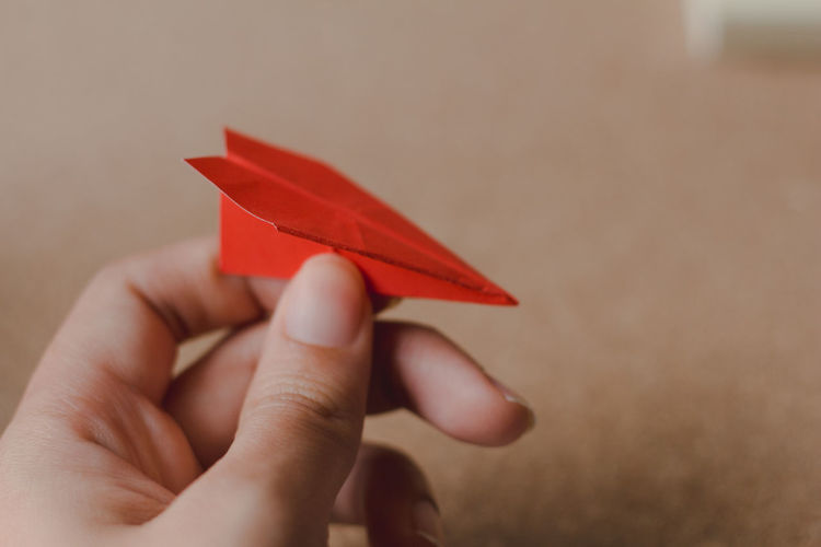 Cropped hand of person holding red origami