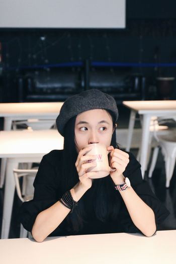 Close-up of young woman drinking coffee while looking away at cafe
