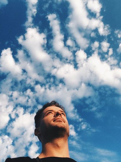 Low angle view of man against cloudy sky