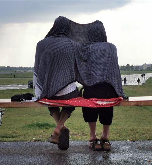 Rear view of couple standing on field against sky