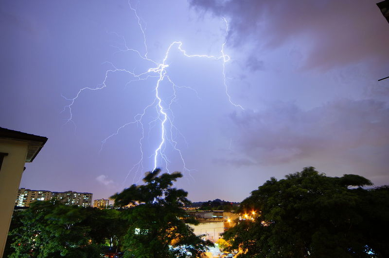 Low angle view of lightning over illuminated buildings at night