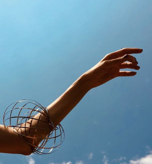 Low angle view of hand against blue sky